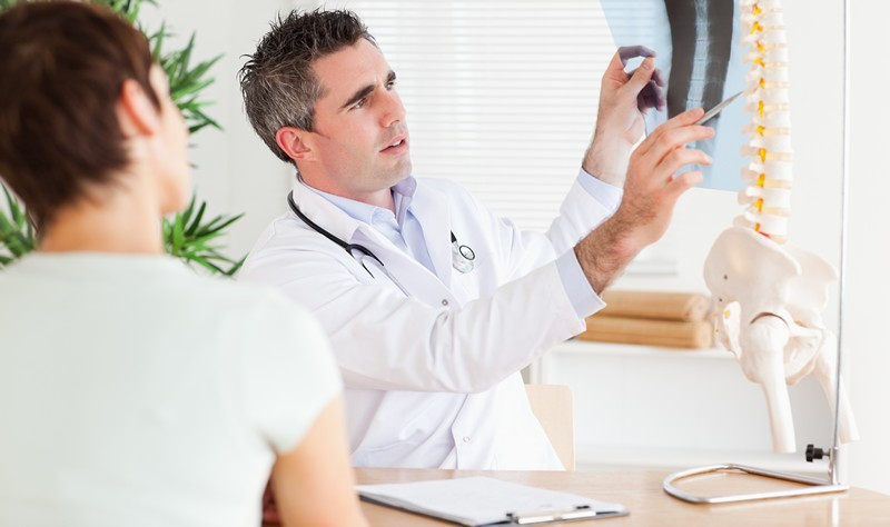 Male Doctor showing a patient a x-ray